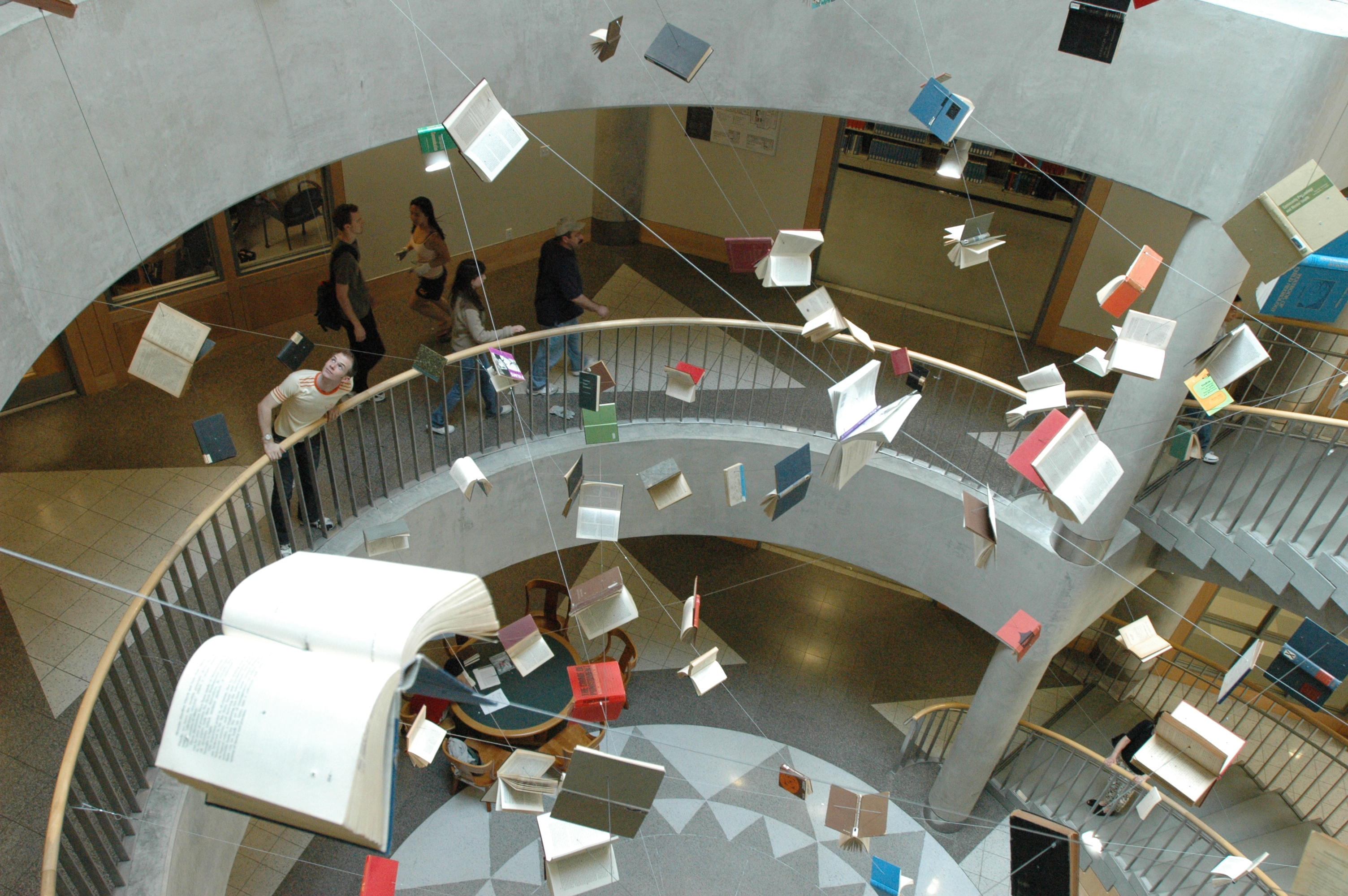 Photo of books seeming to fly through the staircase atrium leading down to Gardner stacks