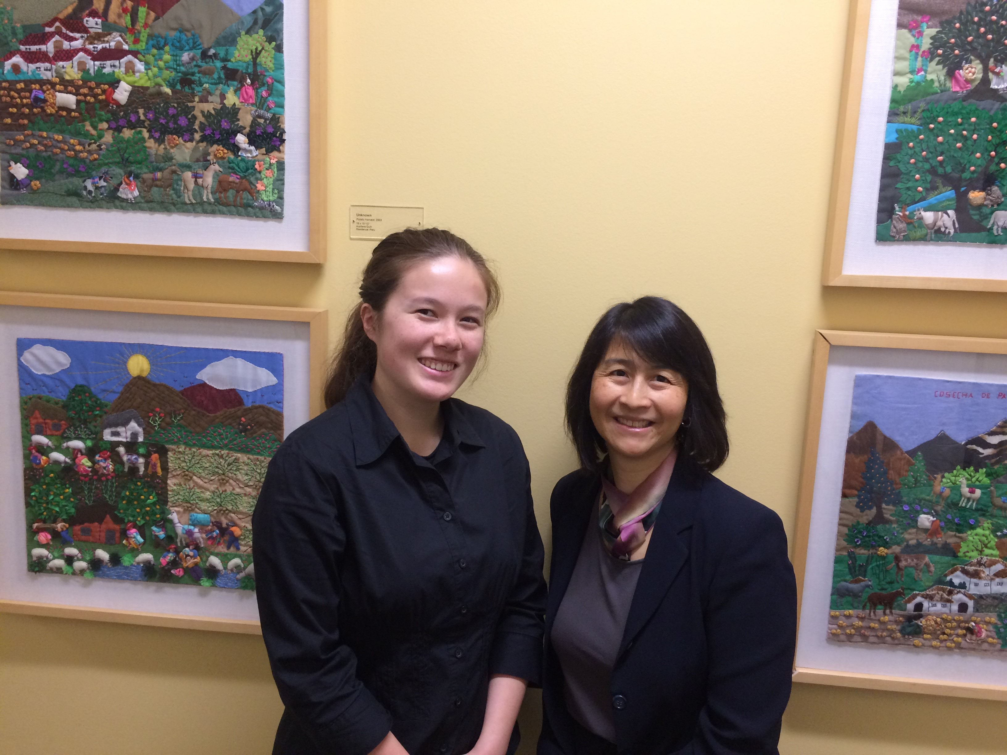 Photo of two women smiling into the camera, with paintings hung on a pale gold wall behind them