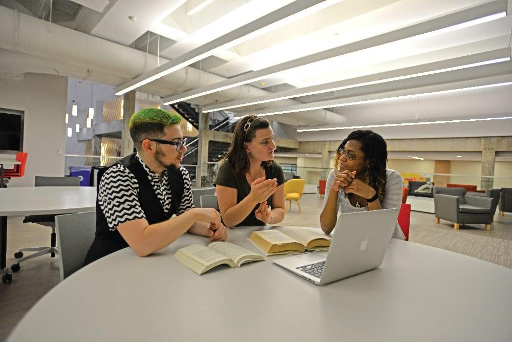 三个学生围着一台笔记本电脑工作