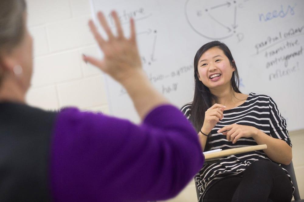 一个学生坐在她身后的一张数学图表的前面, 面对一个模糊的教练, 部分可见