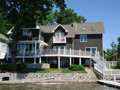 View from the lake of a 2 story traditional style home. A deck wraps around much of the visible side of it. There is also a walkout balcony. There is one tree on this side of the house in addition to some shrubbery.