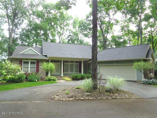 A ranch style home surrounded by trees and tastefully landscaped bushes. There is an attached 2 car garage.