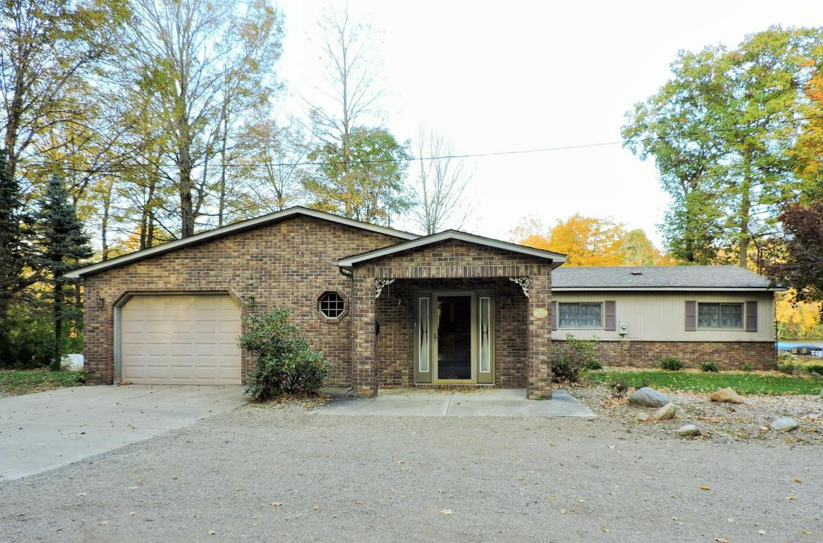 Front view of a ranch house surrounded by trees. House exterior in this shot appears to mostly be brick, but the listing says vinyl. Looks like a glass front door, a few windows with shutters, and one octagonal window with the panes arranged in a sort of grate. Attached garage.
