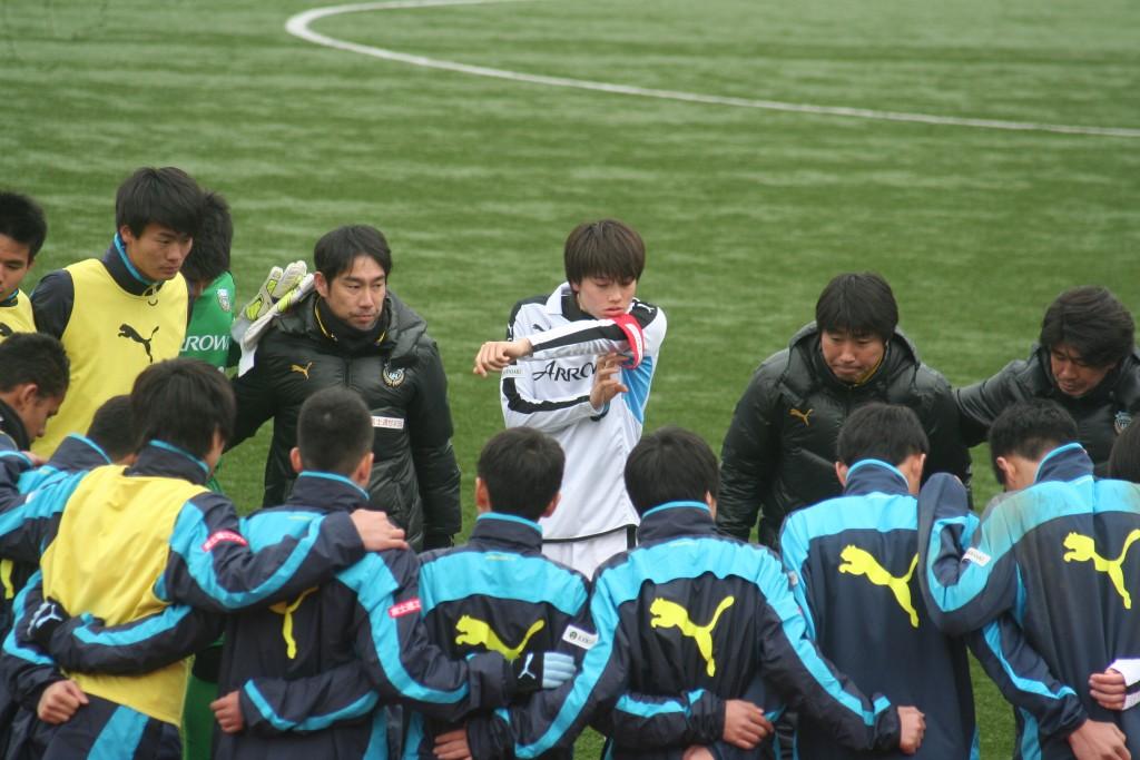 円陣を組む選手たち。田中碧選手がキャプテンマークを巻き直す