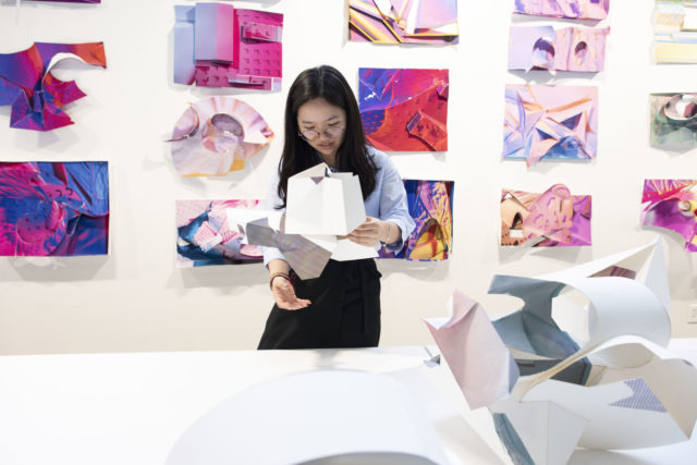 student observing model infront of multicolored pin-up