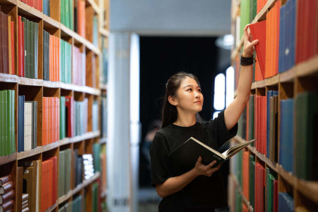 student wearing black in library of books