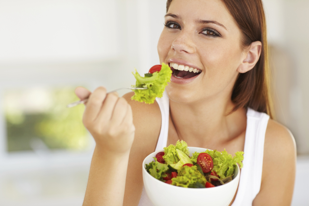 Teenage female eating salad