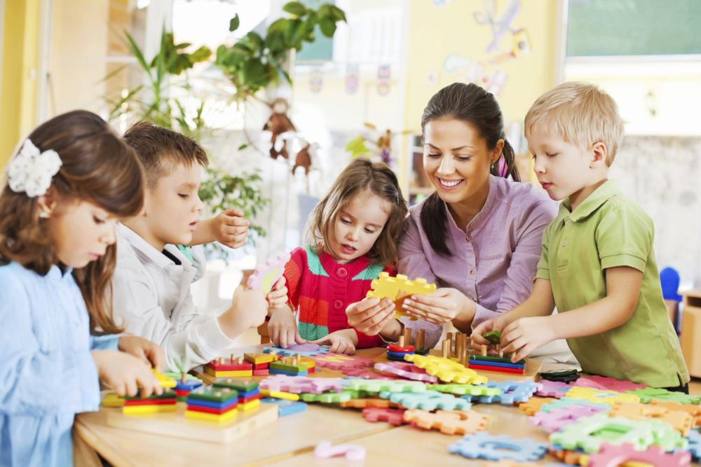 "alt=""a picture of children making puzzle with an instructor, Irvine, CA"""