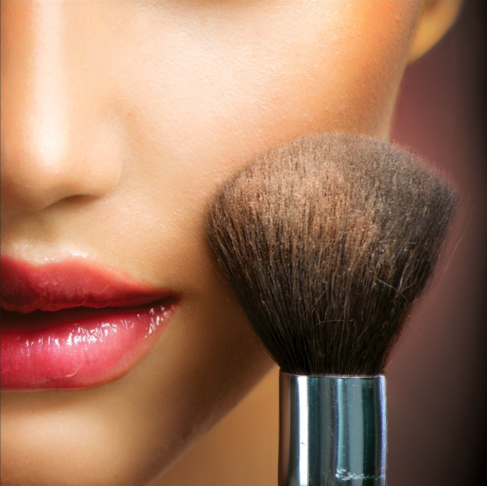 Half of woman's face with a makeup brush next to it