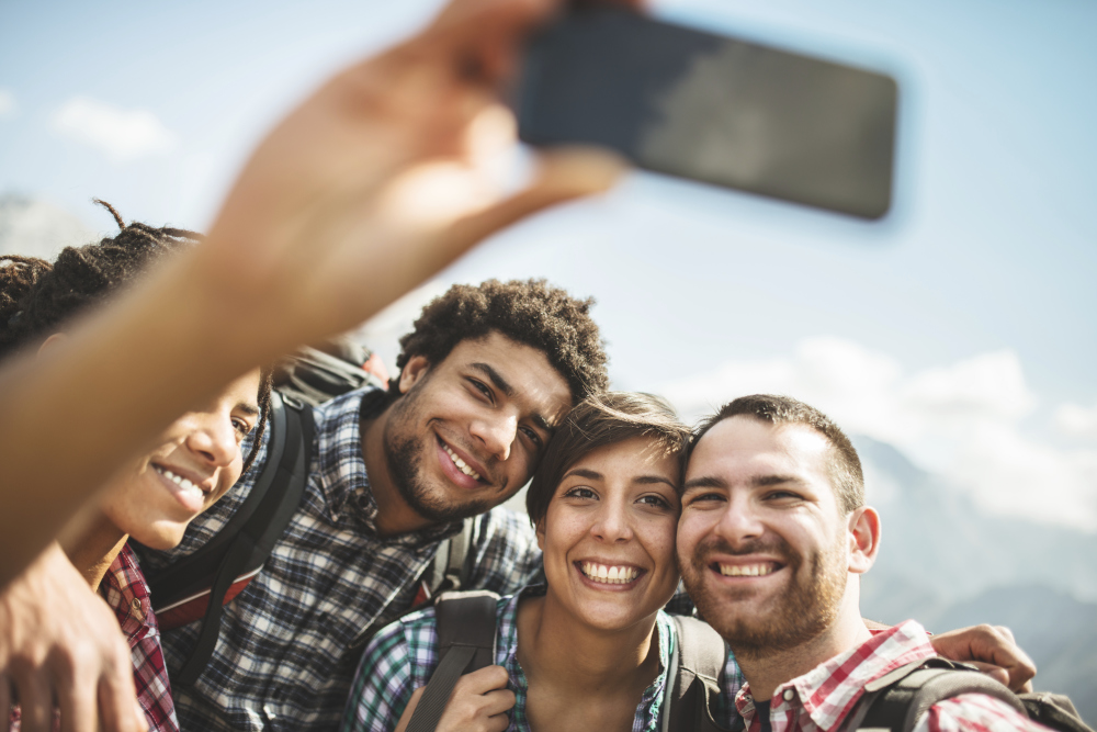 Four young adults. Two couples. Happy. Smiling. Taking selfie.