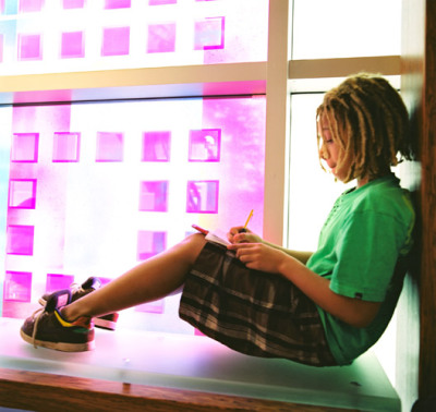 A student enjoys the quiet space for reading in the light of Sarah Hall's solar art glass