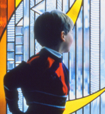 a boy looks in wonder at stained glass