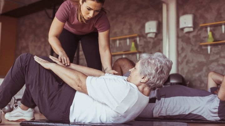 A trainer helps an older woman work out in the gym