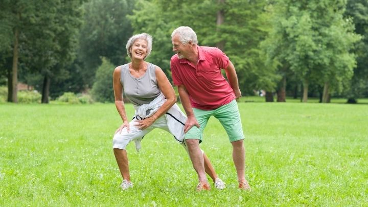An older couple laugh as they work out in the nature