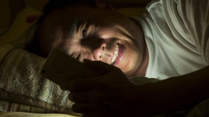 Middle aged man on his smart phone in bed