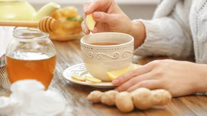 A cup of tea with honey and lemon