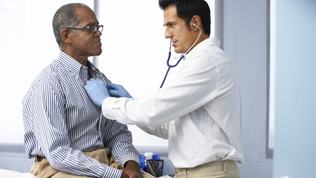A doctor listening to a man's heart