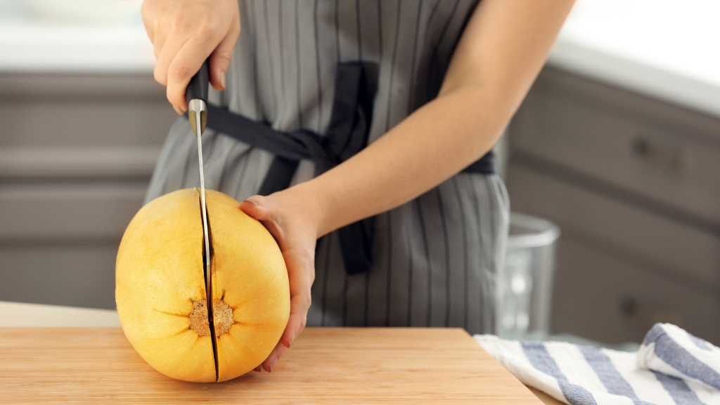 Woman cutting spaghetti squash on a wooden board