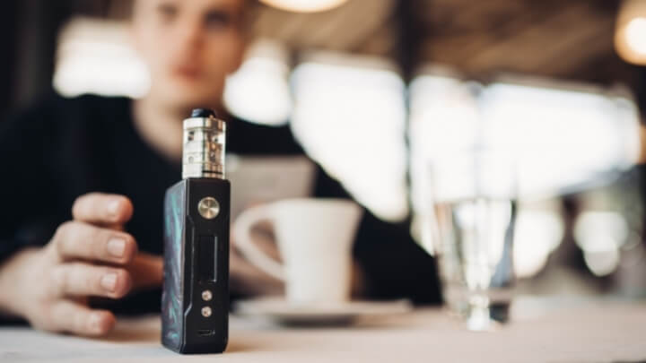 A man reaching to his vaping device