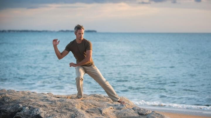 Man doing tai chi on a rock in the beach