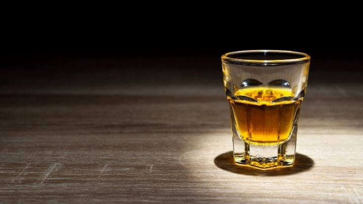 Whisky in a shot glass on wooden table