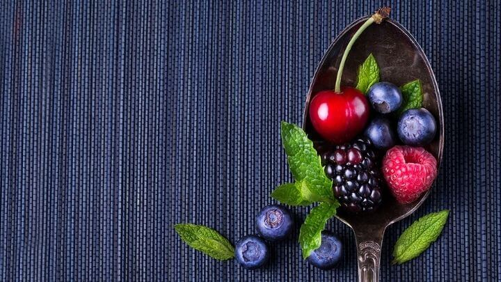 A cherry with mixed berries on a spoon
