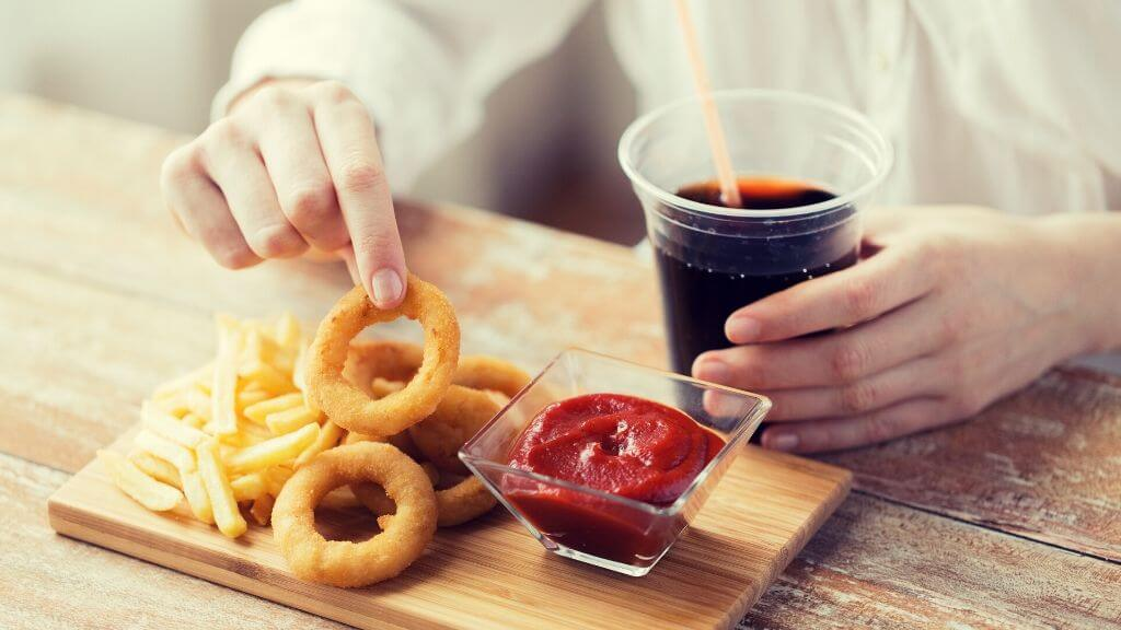 Woman fried fast food and having a diet soda