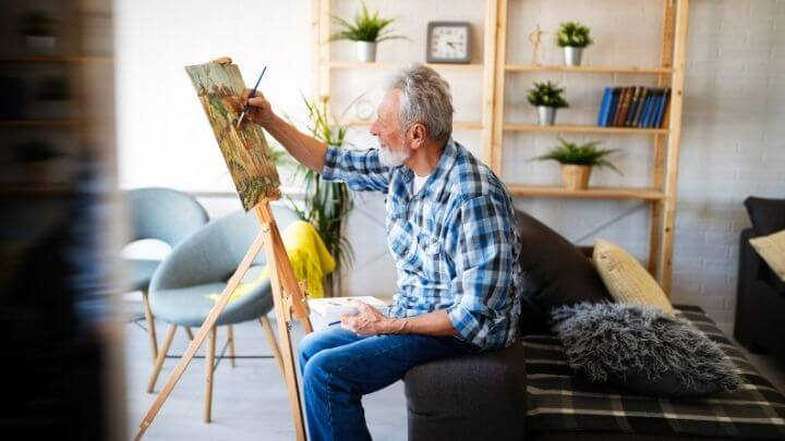 A healthy older man painting at home