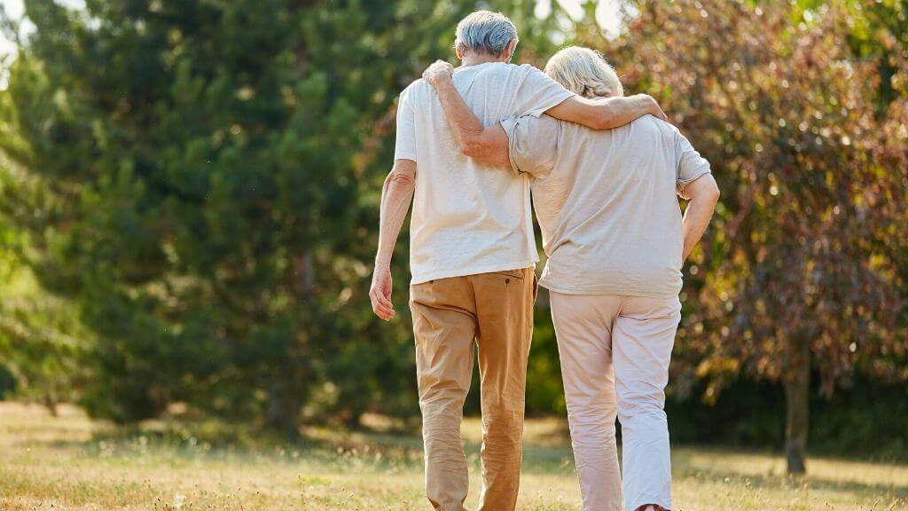 Elderly couple walking in each other's arms