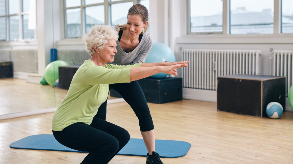 An older woman exercising with the assistance of a physical trainer