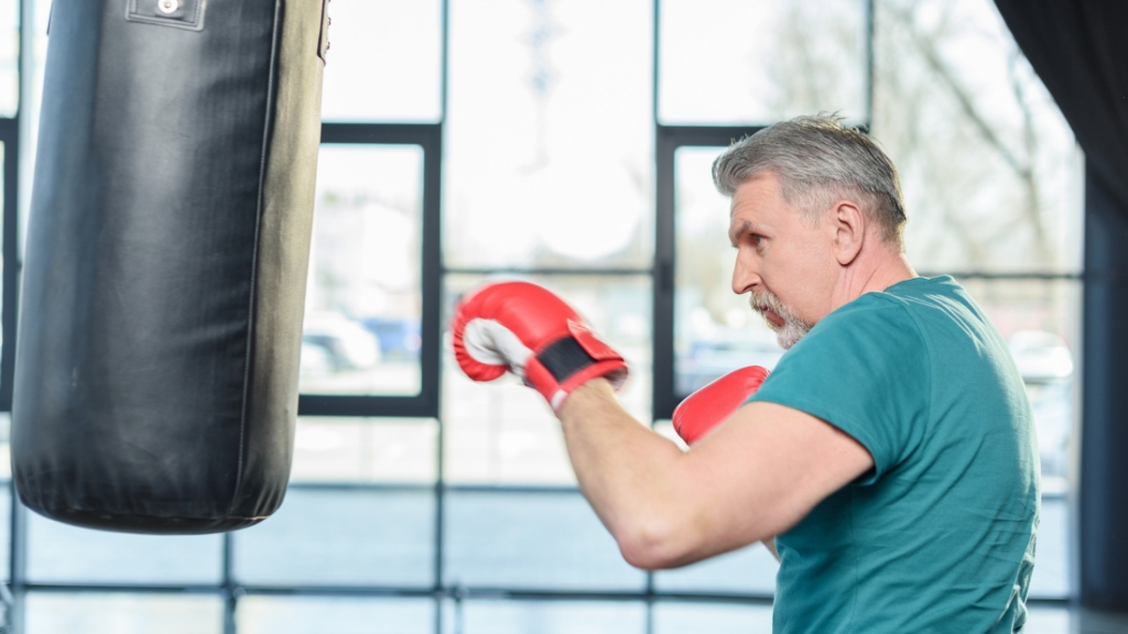 A senior man works out with a punch bag