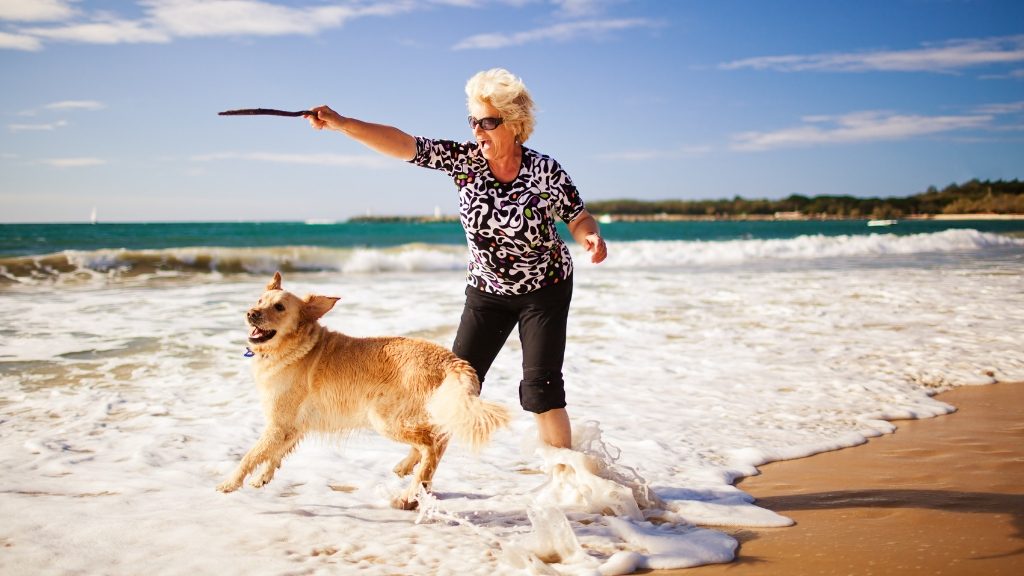 A senior woman playing with her dog in the beach