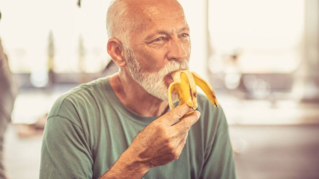 A middle-aged man eating a banana