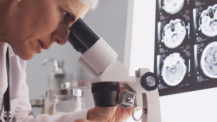 A scientist looking into microscope