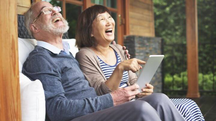 Elderly couple laughing at their porch
