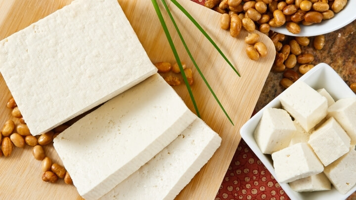 Tofu slices next to soy beans