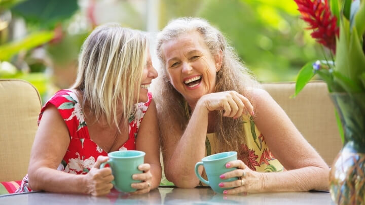 2 older women laughing over coffee