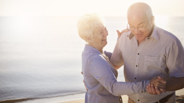 A senior couple dancing by the sea