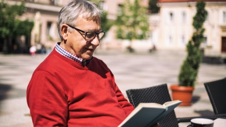 Older man reading a book outside