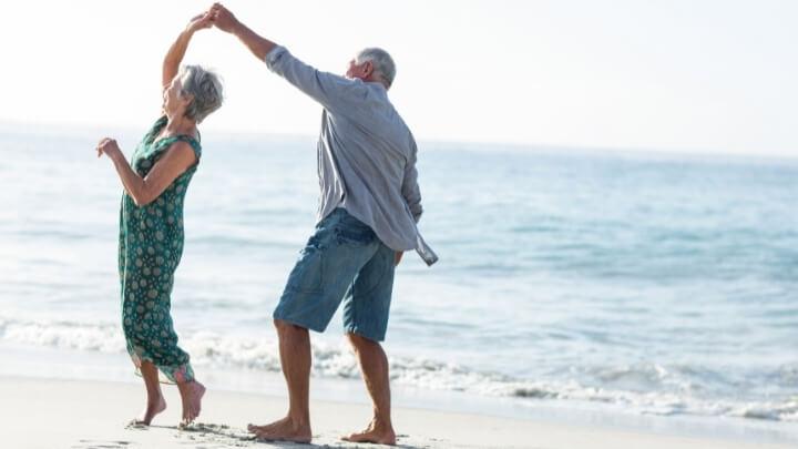 A senior couple dancing on the beach