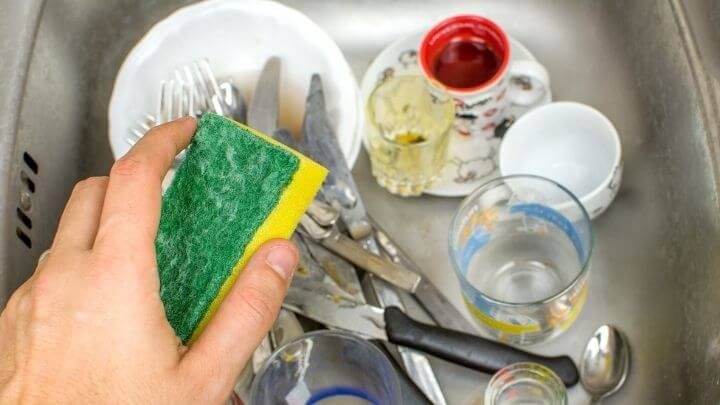 Man holding a sponge, about to do the dishes