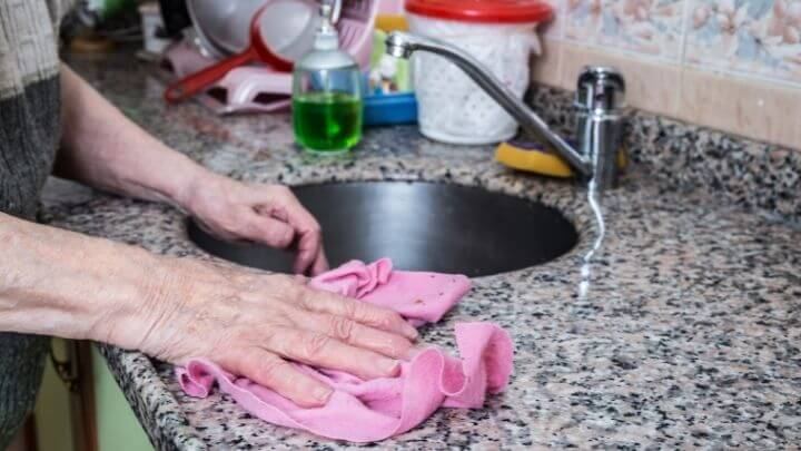 Woman cleaning the kitchen with a soft rag