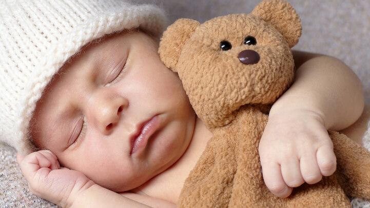 Baby sleeping with a teddy bear