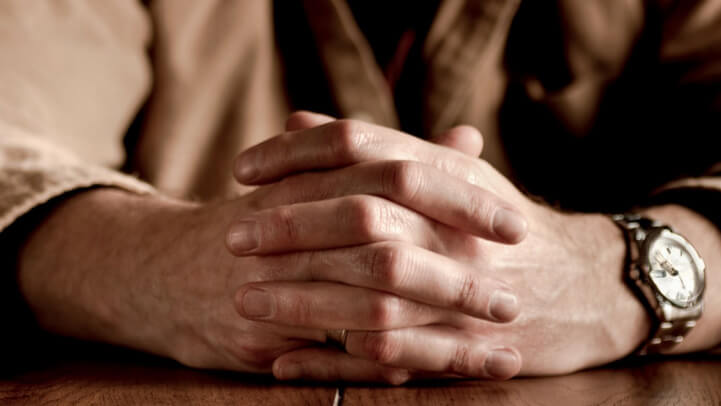 A man's hands with crossed fingers