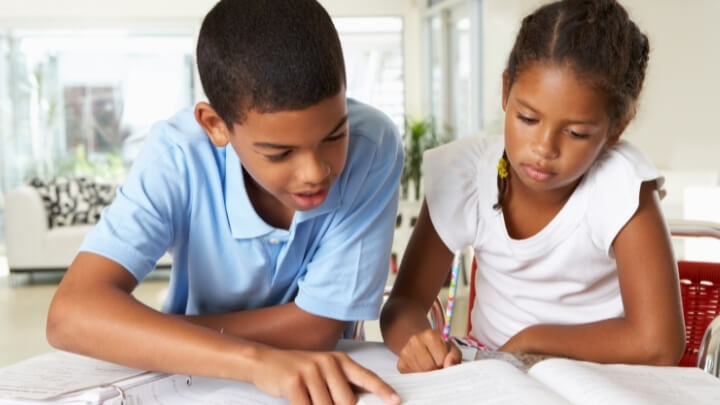 A big brother helping his sister with homework