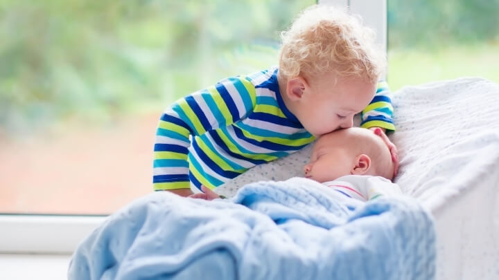 A little kid kissing his baby brother