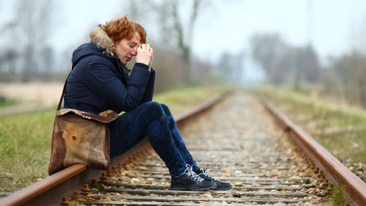 A middle aged woman crying while sitting on the railroad tracks