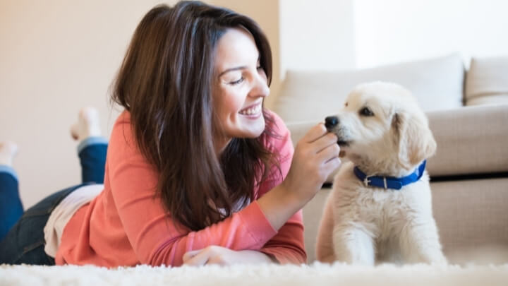 A woman giving a treat to her dog
