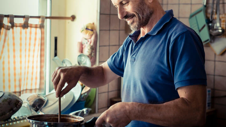 A happy man cooking at home