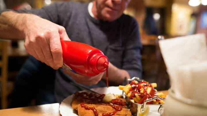 A man pouring ketchup on fried food
